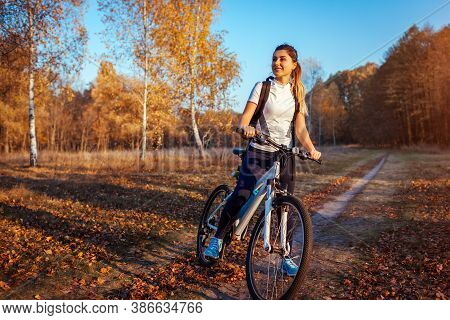 Riding Bicycle In Autumn Forest. Young Woman Having Rest After Workout On Bike Enjoying Nature. Heal