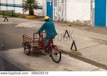 Manta, Ecuador - December 2, 2008: Man Dressed In Blue And Yellow Cap Rides Red Delivery Tricycle In