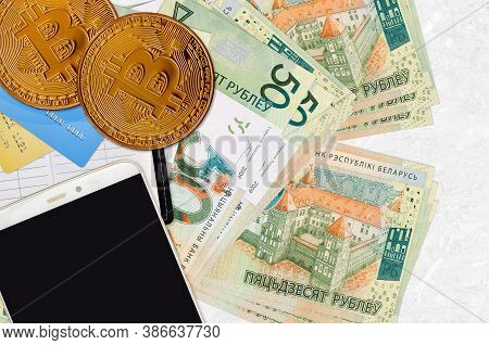 50 Belorussian Rubles Bills And Golden Bitcoins With Smartphone And Credit Cards. Cryptocurrency Inv