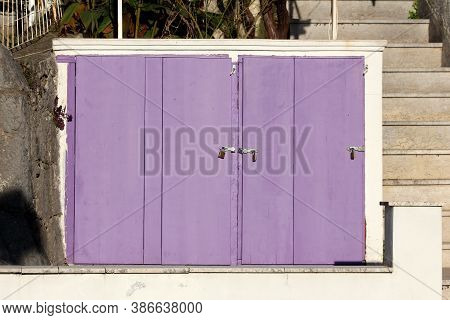 Freshly Painted Light Purple Wooden Doors On Old Storage Area Locked With Three New Padlocks Located