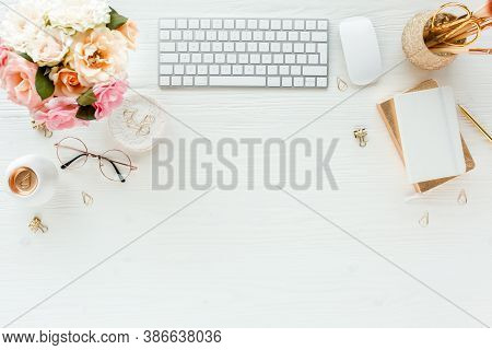 Flat Lay Womens Office Desk. Female Workspace With Computer, Pink Roses Flowers, Accessories, Golden