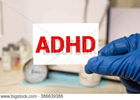 Young Boy Holds Adhd Text Written On Sheet Of Paper. Adhd Is Attention Deficit Hyperactivity Disorde