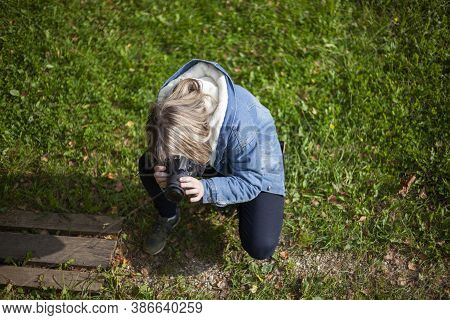 The Photographer Takes Pictures Of The Grass. The Girl Learns To Photograph. Teenager With A Camera