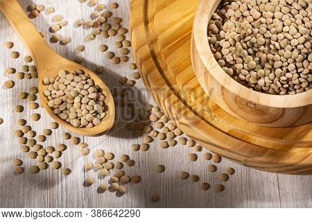 Uncooked Lentils In The Bowl And Wooden Spoon - Lens Culinaris