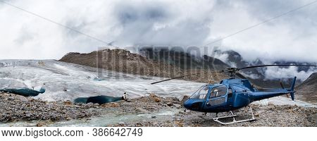 Helicopter At The Base Of A Mountain Glacier Near Whistler, Bc