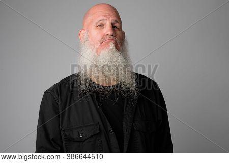 Face Of Mature Bald Man With Long Beard Making Smug Expression