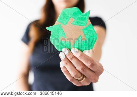 Sustainable Development Concept, Woman Holding A Recycle Sign Towards The Camera Shot At Shallow Dep