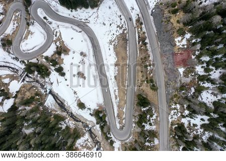 delivery truck on curvy alpine road on winter aerial top view transportation low traffic concept