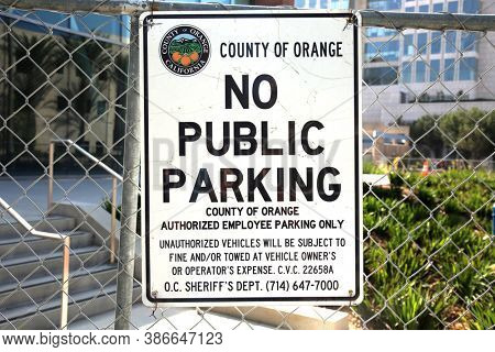Santa Ana, California / USA - September 23-2020: County Of Orange NO PUBLIC PARKING Sign. Orange County California No Public Parking Sign posted on a chain link fence. Editorial Use Only.