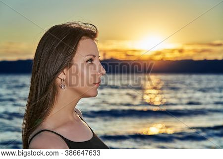 Portrait Of A Young Brunette Woman Against The Backdrop Of The Sunset Over A Large Lake. Closeup.