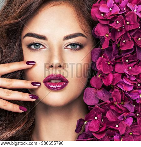 Beautiful  woman with purple make-up of lips and fingernails. Closeup woman's portrait with flowers. Young caucasian gorgeous attractive Model. Vivid make-up. . Violet fingernails