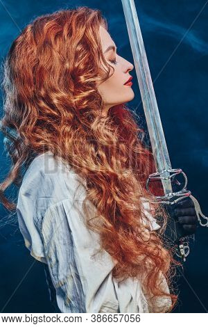 Profile portrait of a beautiful and brave red-haired woman with a battle epee (rapier). Historical reconstruction of the 16-17th centuries.