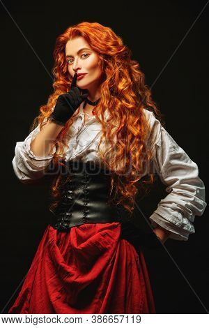 Portrait of a beautiful young woman with magnificent red hair in a historical costume of 16-17th centuries smiling at camera. Studio portrait on a black background.