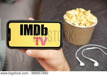Imdb Tv Logo On The Mobile Phone Screen With Popcorn Box And Apple Earpods On The Background. Leisur