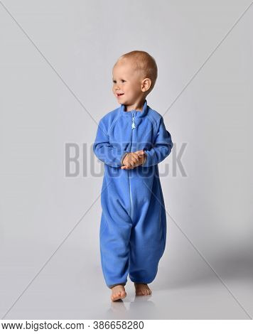 Joyful Smiling Baby Boy In Blue Fleece Jumpsuit Walks Towards Camera Holding Hand In Hand Clapping H