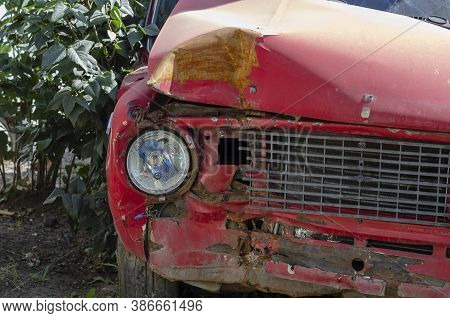 The Front Of The Car After A Road Accident. Red Sedan With Significant Damage To The Headlight And R