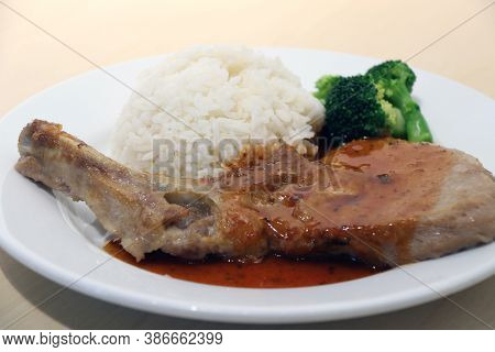 Pork Chop Steak White Rice And Green Broccoli In The Dish On The Wooden Table. Steak Is High Quality