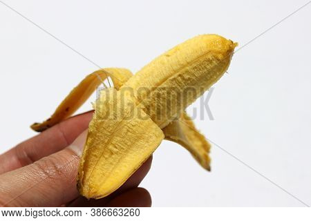 One Pisang Mas Banana Peeled In Hand Isolated On The White Background. Golden Banana On The White Ba