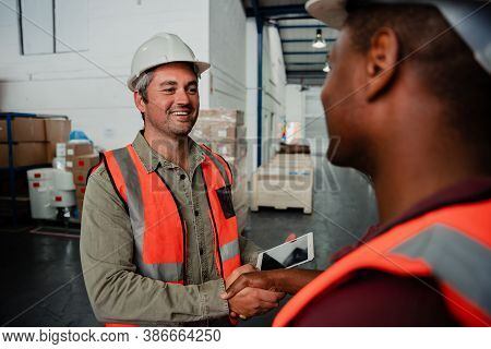 Caucasian Business Man Handshaking Co-worker After Making Successful Business Deal In Factory Shop