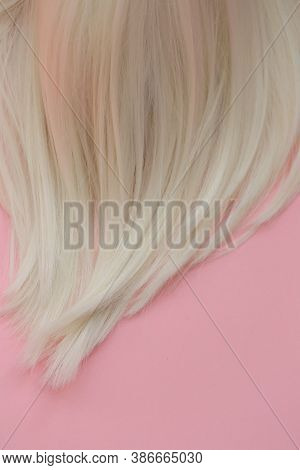 Blond Hair . Blond Hair Texture. A Lock Of White Hair On A Light Pink Pastel Background.hairdressing