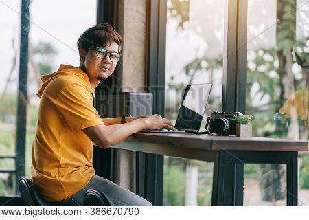 Happy Asian Freelance Man Looking At The Camera, Rewriting Content In Social Network Via Laptop Comp