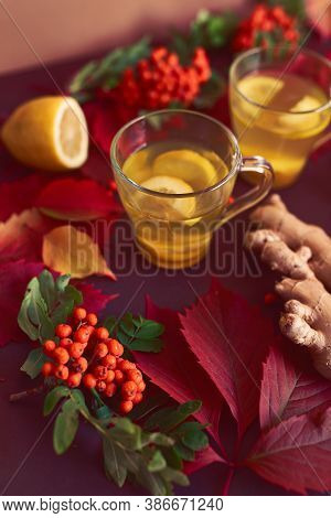 Autumnal Composition With Two Cups Of Ginger Tea, Lemon, Ginger And Red Leaves