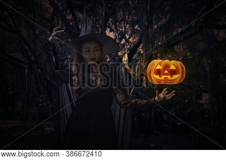 Halloween Witch With Pumpkin Monster Head Standing Over Lips Standing Over Spooky Dark Forest With T