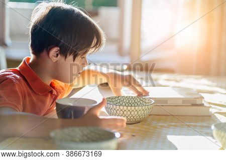 Thoughtful Child Boy Wearing An Orange T-shirt With Down Syndrome Sitting At Table And Reading Book