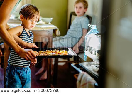 Cute Little Preschooler Boy In Striped T-shirt Help His Mother At Kitchen. Cook At Home. Young Woman