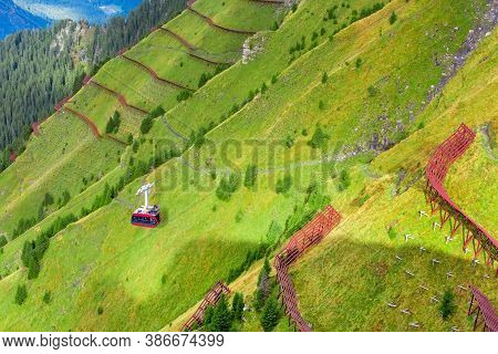 Red Cable Car From Mountain Village Wengen To Viewpoint On Cliff In Mannlichen, Switzerland, Bernese