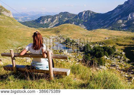 Girl Relaxing After Hike Looking To Mountain View. Traveler Sitting On Wooden Bench Enjoying Beautif