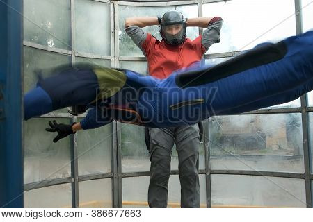 Young Man With Instructor Is Flying In Aerodynamic Tube, Professional Lesson. Instructor Is Holding