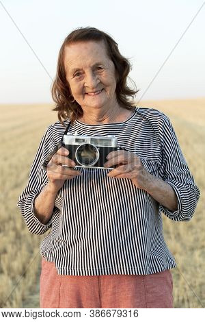 Portrait Of An Elderly Woman With An Analog Camera In The Field.