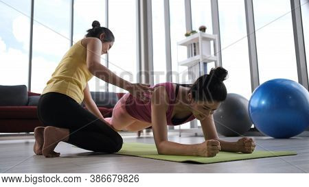 Young Asian Teacher With Student Working Out In Sports Club, Instructor Helping Female Student To Do