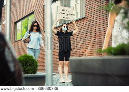 Elon, Wear Your Mask. Dude With Sign - Woman Stands Protesting Things That Annoy Her. Solo Demonstra