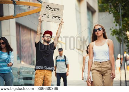 Racism Is A Virus. Dude With Sign - Man Stands Protesting Things That Annoy Him. Solo Demonstration