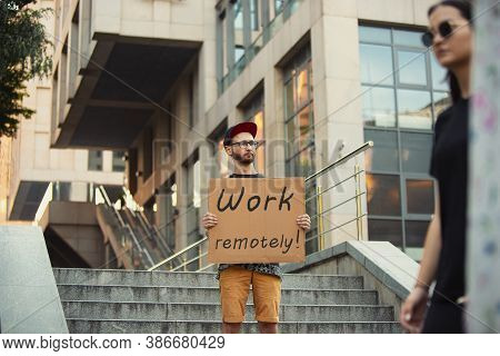 Work Remotely. Dude With Sign - Man Stands Protesting Things That Annoy Him. Solo Demonstration His