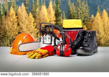 Chainsaw And Protective Clothing, Equipment Of Lumberjack Against Forest Background.