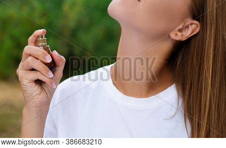 Woman Uses A Bottle Of Perfume At Summer Background