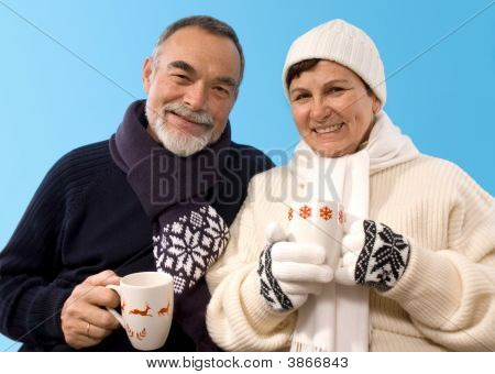Happy elderly couple portrait trinking hot tea poster