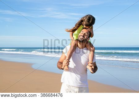 Cute Pretty Girl Kissing Her Dad While Riding On His Neck. Father And Little Daughter Enjoying Leisu
