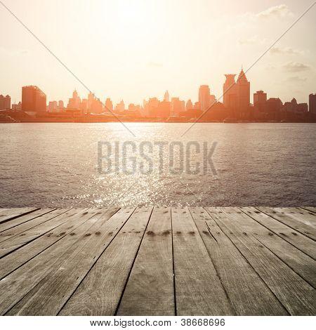 wooden platform before modern city