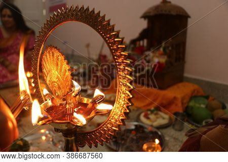 Puja Set Up In Hinduism. Selective Focus On Burning Traditional Brass Lamp Called Diya Surrounded By