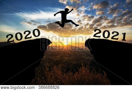 A Young Man Jump Between 2020 And 2021 Years Over The Sun And Through On The Gap Of Hill  Silhouette