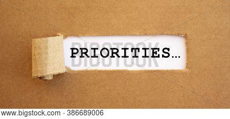 Text Priorities Appearing Behind Torn Brown Paper.