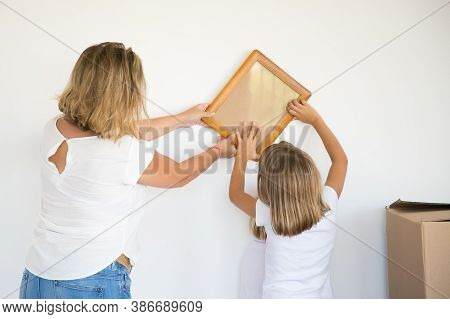 Adorable Little Girl Putting Photo Frame On White Wall With Help Of Mom. Cute Daughter And Blonde Mo