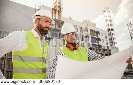 Low Angle Of Men In Waistcoats And Helmets Examining Blueprint While Working On Construction Site To