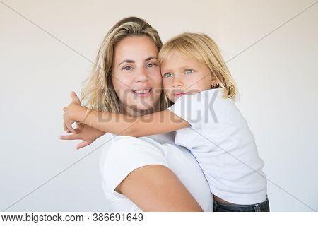 Pretty Blonde Mother Holding Daughter And Looking At Camera. Portrait Of Adorable Little Girl Sittin