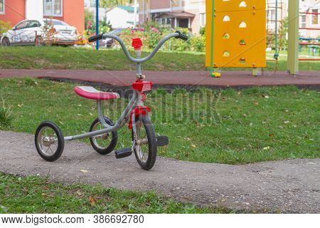 Red Tricycle On The Playground In Summer. A Vehicle For Small Children To Ride.