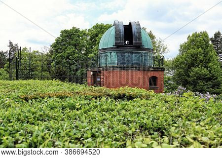 Open Cupola Of The Astronomy Observatory With The Telescope Lens Behind Hedge